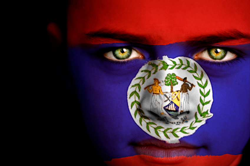 Portrait of a boy with the flag of Belize on his face.